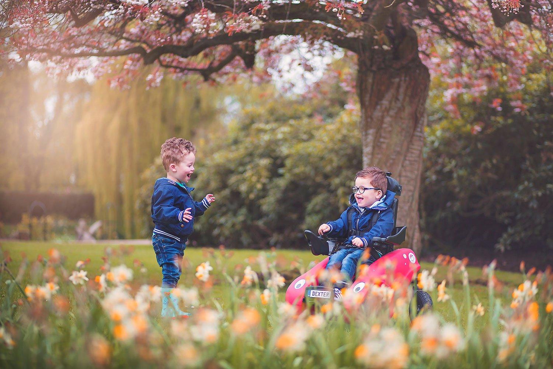 To glade gutter leker utendørs, og den ene sitter i WizzyBug-rullestolen.