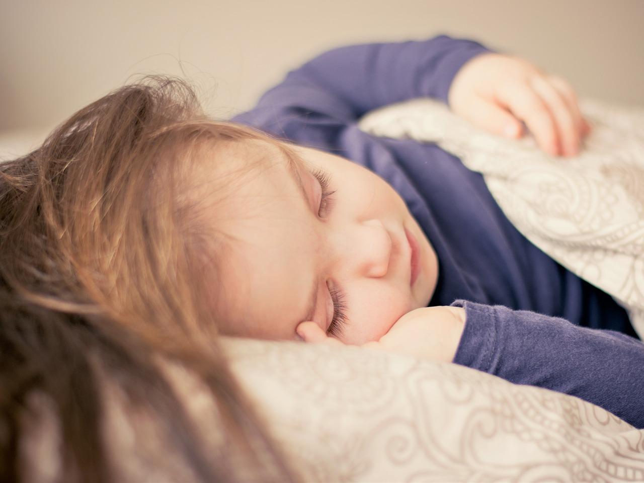 En jente sover søtt på siden, med hånden under hodet, under en dyne.