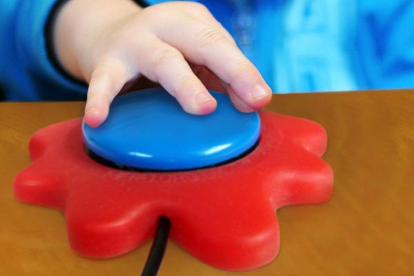 Et barn trykker på en stor, blå bryter.