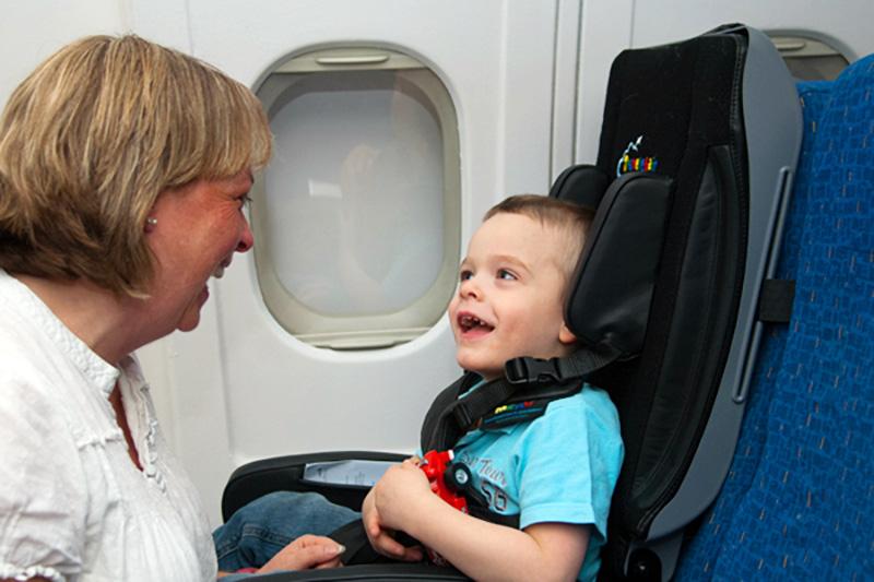 En gutt med spesielle behov reiser i flystolen og ler med sin mor..