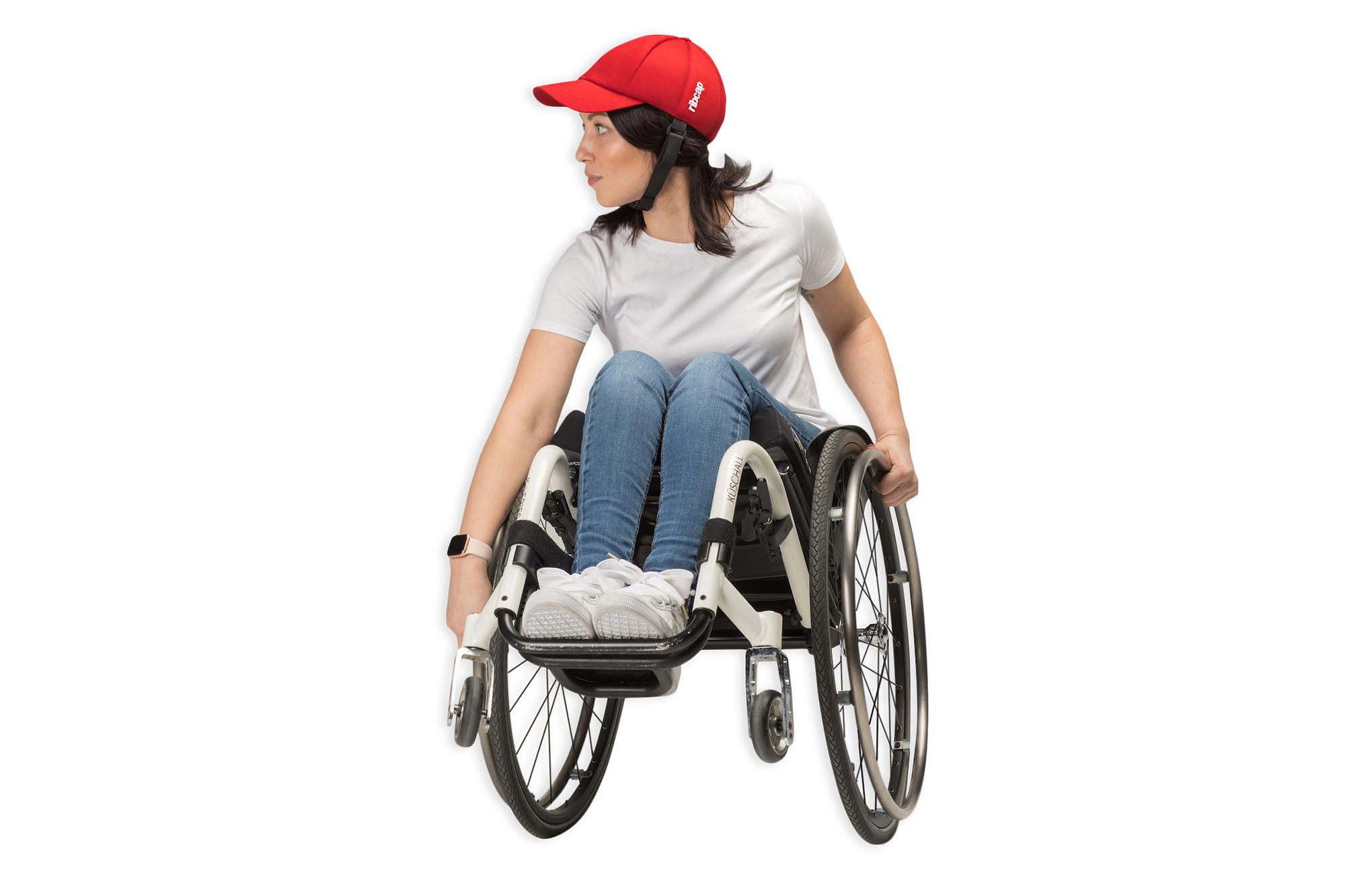 Ung, aktiv kvinne i rullestol iført en rød Ribcap Baseball med hakestropp, som sørger for stilsikker beskyttelse av hodet.